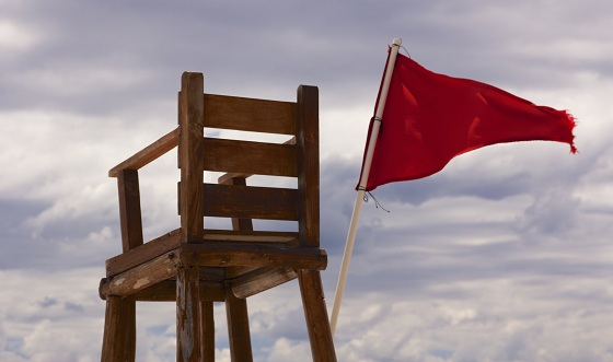 Lifeguard chair sitting empty with a red flag streaming in the wind, showing unsafe conditions for swimming, before the background of an overcast sky.