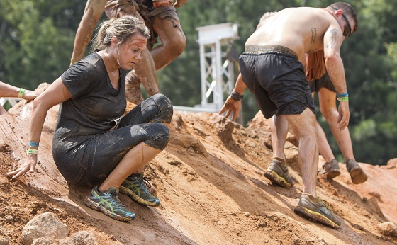 Conyers, GA, USA - August 22, 2015: Competitors carefully make their way down a large slippery dirt mound at the Rugged Maniac Obstacle Course race in Conyers, GA.