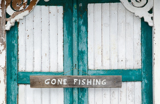 Gone fishing sign at weathered doors